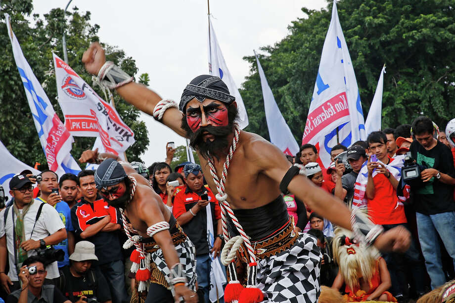 Traditional Javanese dancers perform in front of the Presidential Palace during a labor demonstration on May 1, 2013 in Jakarta, Indonesia.  Tens of thousands of workers and labor activists marched through Jakarta's central business district, demanding the implementation of higher minimum wages and better working conditions. Photo: Ed Wray, Getty Images / 2013 Getty Images