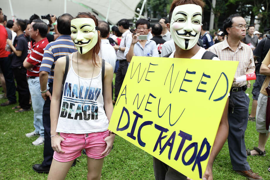 People put on a Guy Fawkes masks during a protest against the government's White Paper on Population and labour-related matters that affect Singaporeans at Speakers' Corner in Hong Lim Park on May 1, 2013 in Singapore. Thousands of protesters gathered today in an inaugural labour day protest against the 6.9 million population government white paper that revealed it could increase 30% to 6.9 million by 2030, angering residents who already see a strain on housing, transportation and healthcare. Photo: Suhaimi Abdullah, Getty Images / 2013 Getty Images