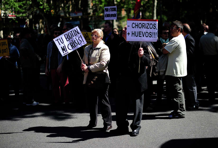 "Protesters hold placards reading ""Your loot, my crisis"" (L) and ""Less thieves, more courage!"" during a Labour Day march in the centre of Barcelona on May 1, 2013. Tens of thousands protested across the globe for May Day to press for workers' rights amid tough economic times and to back an array of other causes. Photo: JOSEP LAGO, AFP/Getty Images / 2013 AFP"