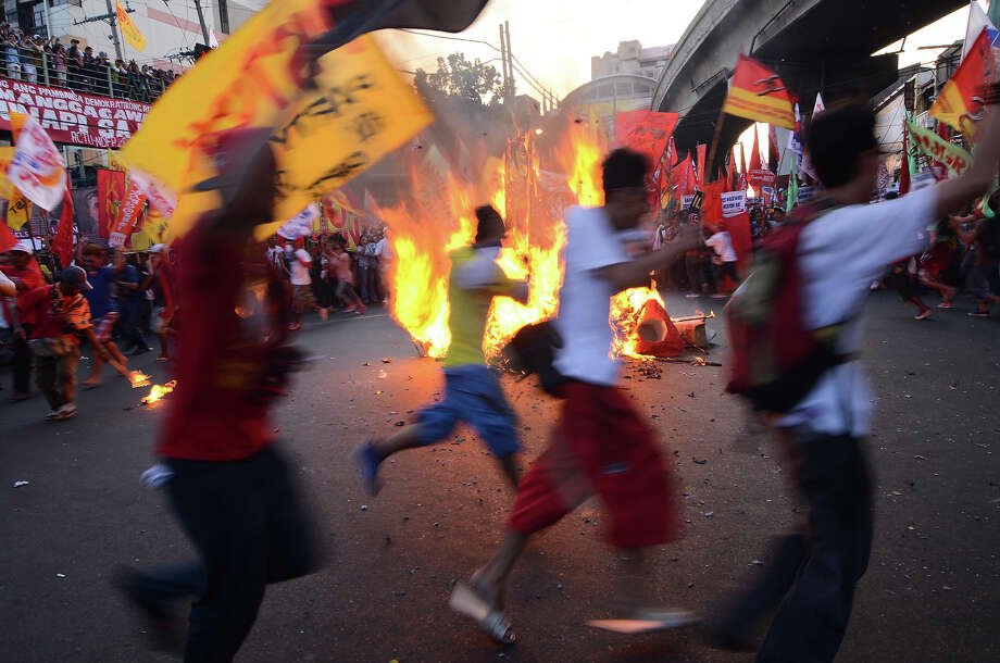 Protestors cricle around a burning effigy of Philippine president Benigno Aquino and US president Barack Obama on May 1, 2013 in Manila, Philippines. Philippine workers unions gather in the streets of Manila to demand, among other things, better pay, an end to contractualization and layoff and the lowering of prices of basic commodities. Labor day is celebrated across South East Asia on May 1st and is seen as an opportunity to acknowledge the social and economic accomplishments of the workers. Photo: Dondi Tawatao, Getty Images / 2013 Getty Images