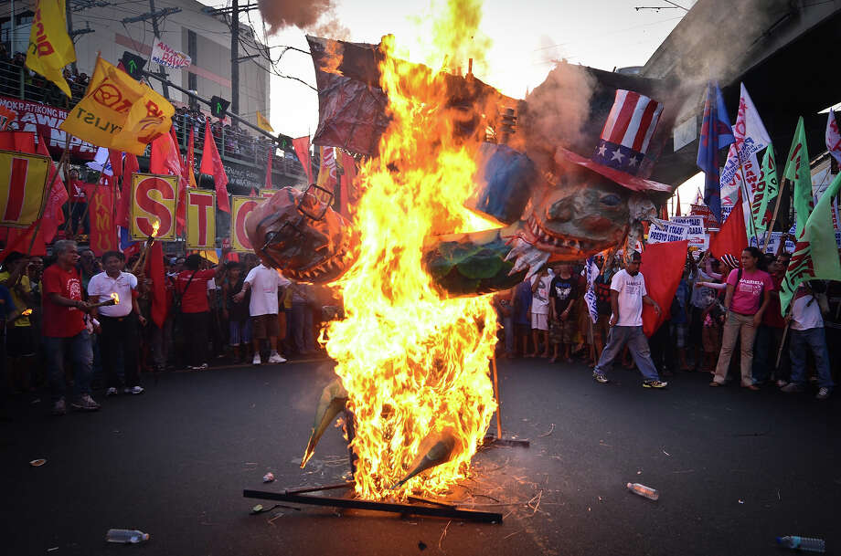Protestors circle around a burning effigy of Philippine president Benigno Aquino and US president Barack Obama on May 1, 2013 in Manila, Philippines. Philippine workers unions gather in the streets of Manila to demand, among other things, better pay, an end to contractualization and layoff and the lowering of prices of basic commodities. Labor day is celebrated across South East Asia on May 1st and is seen as an opportunity to acknowledge the social and economic accomplishments of the workers. Photo: Dondi Tawatao, Getty Images / 2013 Getty Images