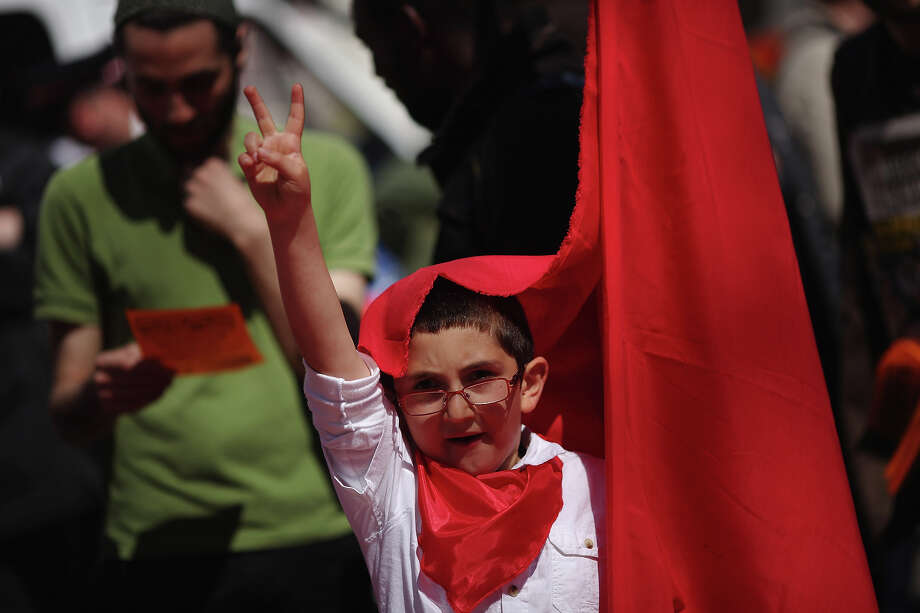 A young protestor flashes the v-sign as protesters gather at the start of the annual May Day march in Clerkenwell on May 01, 2013 in London, England. Students, trade unionists, pensioners and activists staged a march through central London before gathering in Trafalgar Square to hear speeches. Photo: Dan Kitwood, Getty Images / 2013 Getty Images