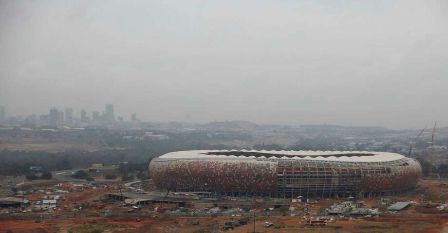 Soccer City City Stadium, foreground, on the edge of Soweto, South Africa was the site of the opening and closing matches.  of the 2010 World Cup. Photo: DENIS FARRELL, AP / AP