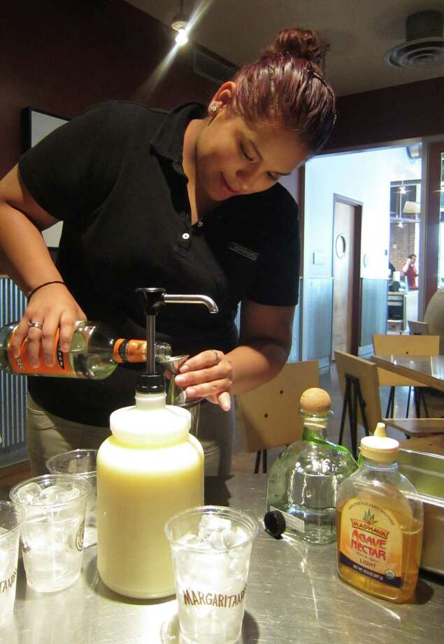 Sandra Maya, manager of the Chipotle Mexican Grill at 909 Texas Ave., makes a hand-shaken magarita with Patron tequila, agave nectar, Triple sec and fresh citrus juice.  The top shelf magaritas will be rolled out nationally beginning April 29, 2013. Photo: Syd Kearney