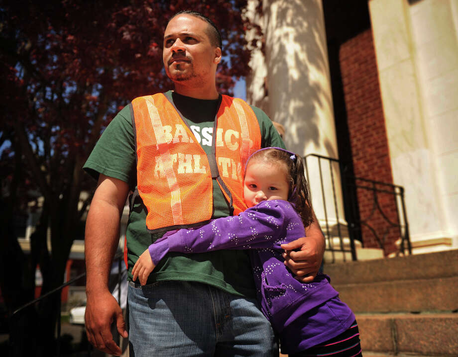 St. V Padilla, head teacher at the ABCD Head Start daycare at Bassick High School, comforts Maneldaliz Mejia, 4, as she waits to be picked up following  a bomb threat evacuation of the school in Bridgeport, Conn. on Wednesday, May 1, 2013. Daycare children were evacuated down Fairfield Avenue from the school to the front steps of the Klein Memorial Auditorium. Photo: Brian A. Pounds / Connecticut Post