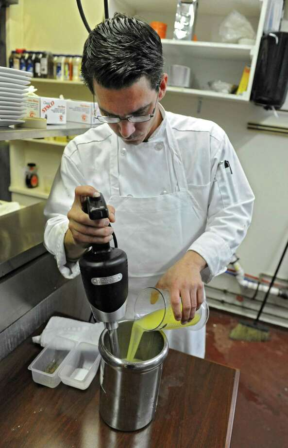 Chef Brian Bowden of Javier's restaurant makes part of the sauce for a jumbo lump crab cake dish on Thursday, April 25, 2013 in Saratoga Springs, N.Y. (Lori Van Buren / Times Union) Photo: Lori Van Buren / 0022145A