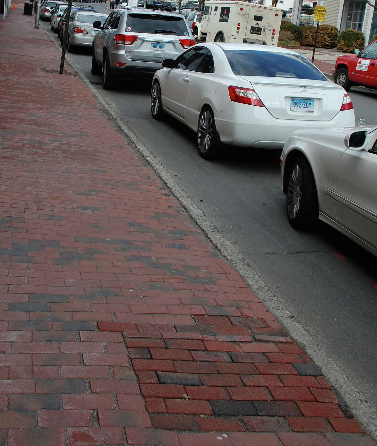 Newer bricks in Main Street sidewalks mark the spots where trees were removed --- without the required permission, according to a new report by the Westport Tree Board.