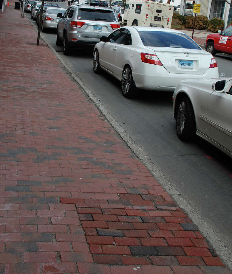Newer bricks in Main Street sidewalks mark the spots where trees were removed --- without the required permission, according to a new report by the Westport Tree Board. Photo: File Photo / Westport News contributed