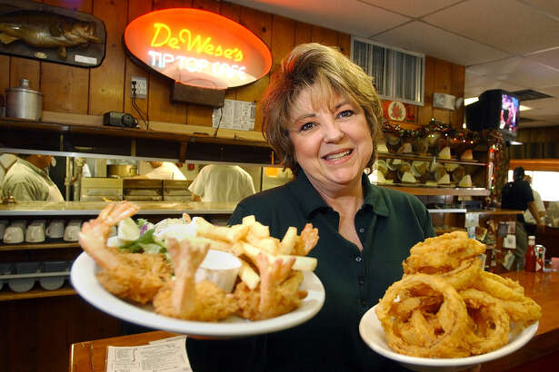 DeWese's Tip Top Cafe's Linda DeWese holds an order of fried shrimp and onion rings - two of the more popular dishes at the restaurant. The eatery will be celebrating their 65th anniversary in 2003. Photo taken Saturday, January 4, 2003. (Kin Man Hui/staff)