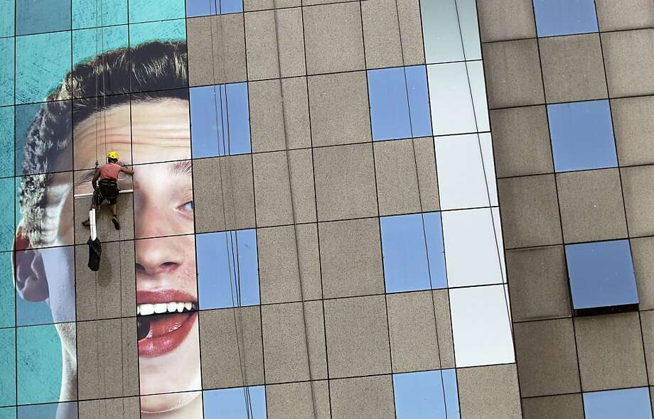 Stop unrolling your eyes at us, buddy: A billboard worker pastes an ad on the facade of a building in Belgrade, Serbia. Photo: Darko Vojinovic, Associated Press