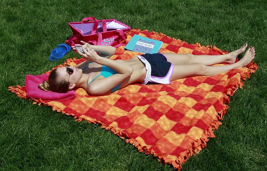 Rockhurst University junior Abby Stroud of St. Louis lays out in the sun on a warm spring day Tuesday, April 30, 2013 at Loose Park in Kansas City, Mo. (AP Photo/The Kansas City Star, Rich Sugg) Photo: Fred Blocher, Associated Press
