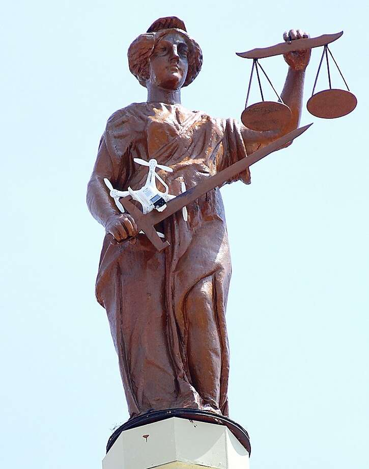 Scale model:A helicopter camera drone nestles behind Lady Justice's sword atop the Marion County Courthouse in Marion, Ohio. Terry Cline was filming the Marion skyline when a gust blew the the remote-controlled craft into the statue's arms. Photo: James Miller/The Marion Star, Associated Press