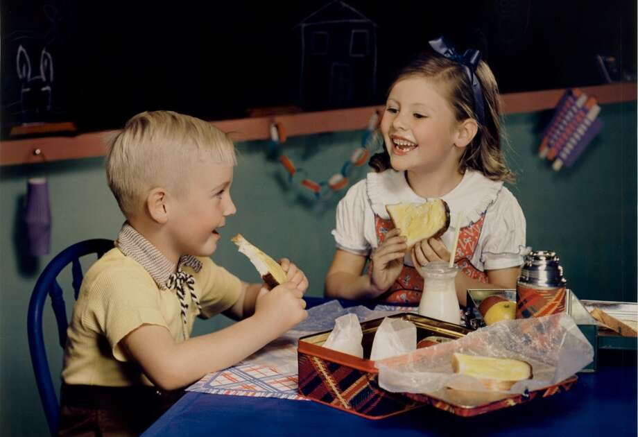 Two school children, a boy and a girl, sit together as they eat lunch from metal lunchboxes, mid 1950s. The photo was taken as part of an advertising campaign for Nucoa Margarine. (Photo by Nickolas Muray/George Eastman House/Getty Images)