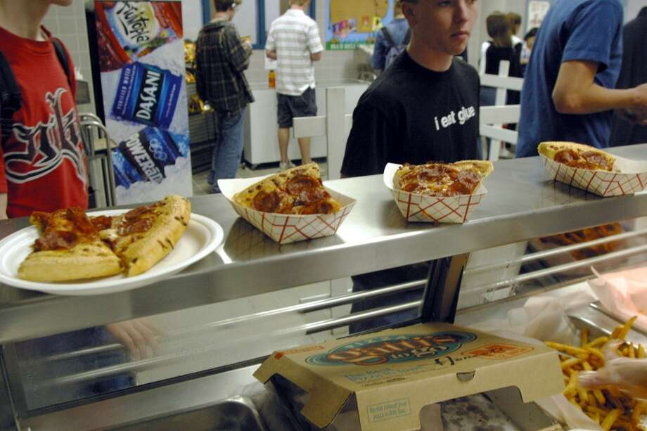 Students line up to receive food during lunch in the cafeteria at Bowie High School  March 11, 2004  in Austin, Texas. The Austin School District is working to make their cafeteria offerings more healthy, but the most  popular foods are still fried chicken strips, pizza, and french fries. Concern about increased levels of childhood obesity in the United States has made the food served in public schools cafeterias a much greater concern. (Photo by Jana Birchum/Getty Images)
