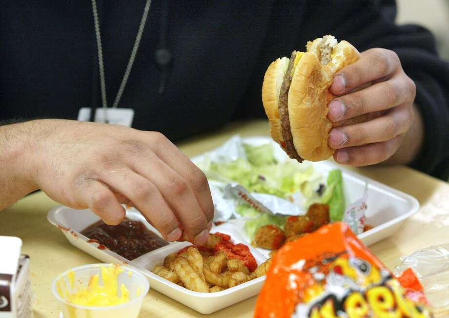 A student eats lunch at Jones College Prep High School April 20, 2004 in Chicago, Illinois. The Chicago Public School system will introduce next fall a new vending policy restricting junk food and a new beverage contract banning carbonated drinks.  (Photo by Tim Boyle/Getty Images)