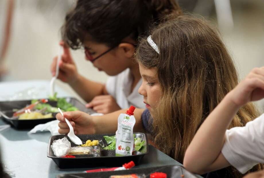 Francesca Virgilio, center, eats a salad during lunch at Sunset Park Elementary School in Miami, Florida, in 2012. The salad bar was introduced at the school to promote healthy eating habits. (Peter Andrew Bosch/Miami Herald/MCT)