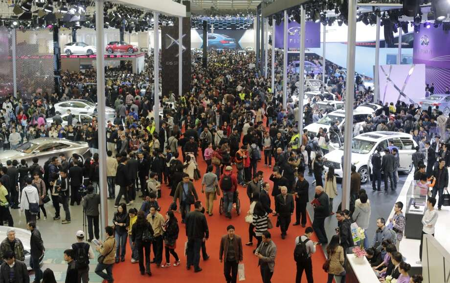 Visitors stroll around vehicles the Shanghai International Automobile Industry Exhibition (AUTO Shanghai) in Shanghai, China Sunday, April 21, 2013. (AP Photo/Eugene Hoshiko)