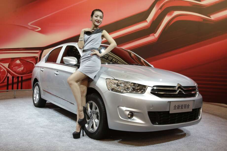 A model poses with a Peugeot C-Elysee displayed at the Shanghai International Automobile Industry Exhibition (AUTO Shanghai) in Shanghai, China Sunday, April 21, 2013. (AP Photo/Eugene Hoshiko)