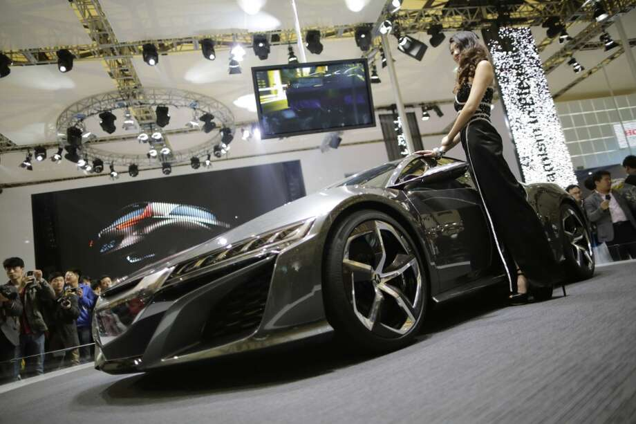 A model poses next to an Acura NSX Concept at the Shanghai International Automobile Industry Exhibition (AUTO Shanghai) in Shanghai, China, Wednesday, April 24, 2013. (AP Photo/Eugene Hoshiko)