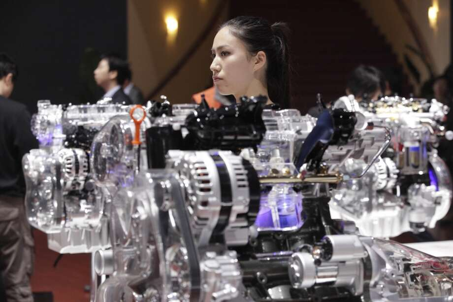 A model stands next to a skeleton model of an engine displayed at the Shanghai International Automobile Industry Exhibition (AUTO Shanghai) media day in Shanghai, China Saturday, April 20, 2013. (AP Photo/Eugene Hoshiko)