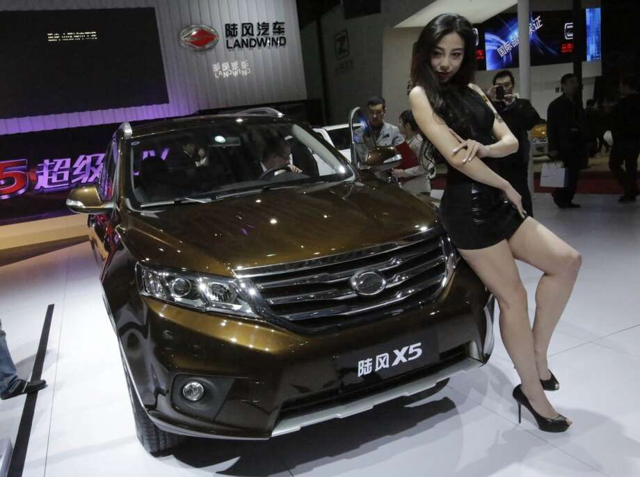 A model poses with the new Landwind X5 SUV at the Shanghai International Automobile Industry Exhibition (AUTO Shanghai) media day in Shanghai, China Saturday, April 20, 2013. (AP Photo/Eugene Hoshiko)
