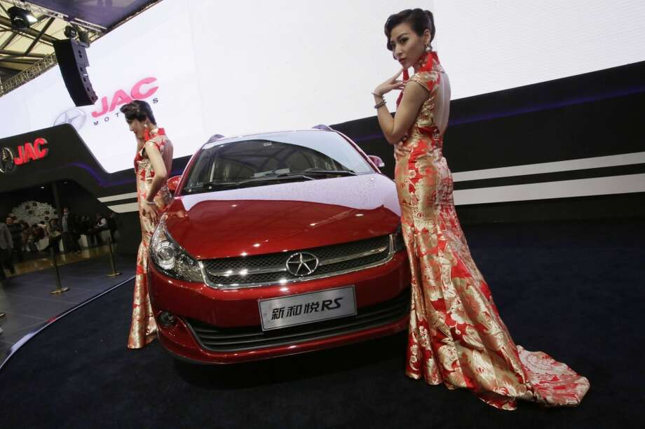 Models pose with a JAC Motors RS car at the Shanghai International Automobile Industry Exhibition (AUTO Shanghai) in Shanghai, China Sunday, April 21, 2013. (AP Photo/Eugene Hoshiko)