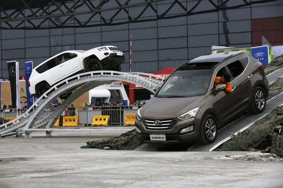 Visitors try our various SUVs at the Shanghai International Automobile Industry Exhibition (AUTO Shanghai) in Shanghai, China Sunday, April 21, 2013. (AP Photo/Eugene Hoshiko)