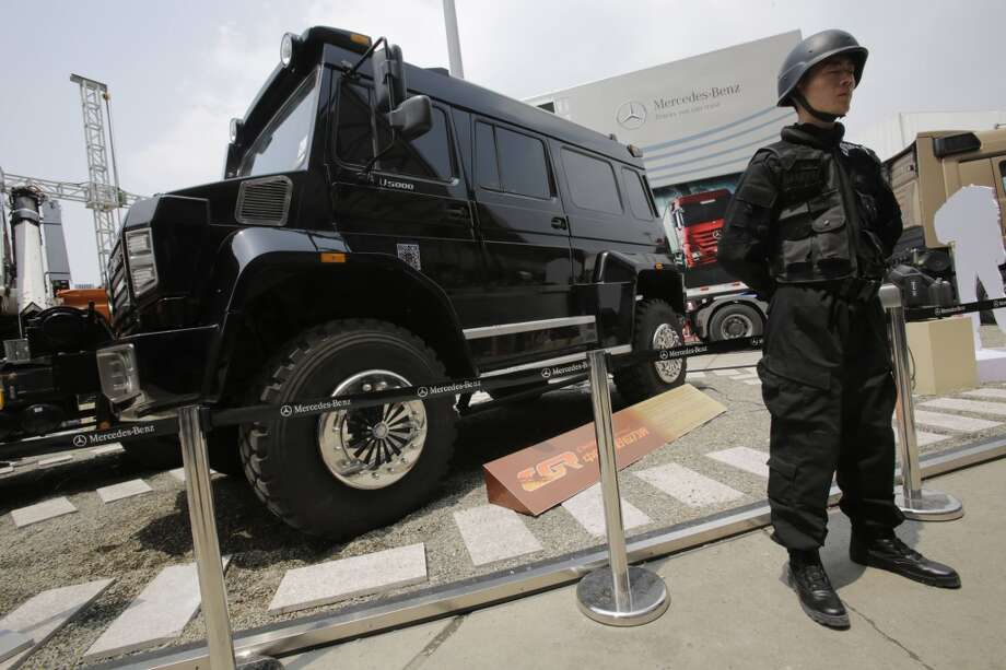 A security guard stands near a Mercedes-Benz Unimog at the Shanghai International Automobile Industry Exhibition (AUTO Shanghai) in Shanghai, China Sunday, April 21, 2013. (AP Photo/Eugene Hoshiko)