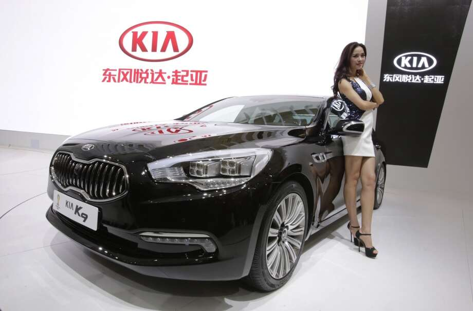 A model poses with a KIA K9 car at the Shanghai International Automobile Industry Exhibition (AUTO Shanghai) in Shanghai, China Sunday, April 21, 2013. (AP Photo/Eugene Hoshiko)