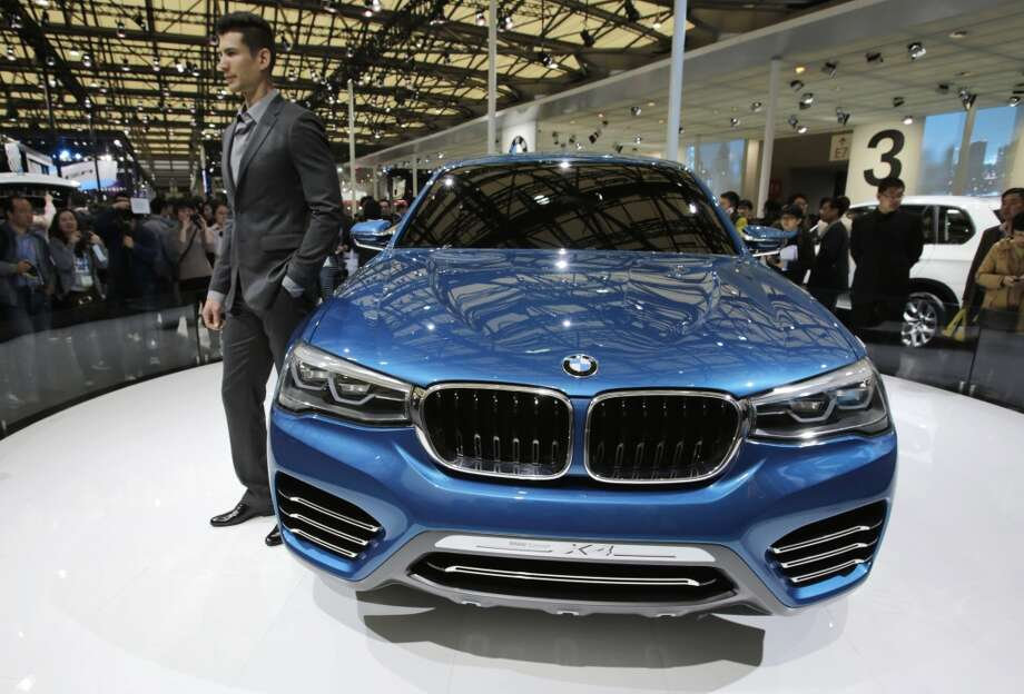 A model poses with new BMW Concept X4 at the Shanghai International Automobile Industry Exhibition (AUTO Shanghai) in Shanghai, China Sunday, April 21, 2013. (AP Photo/Eugene Hoshiko)