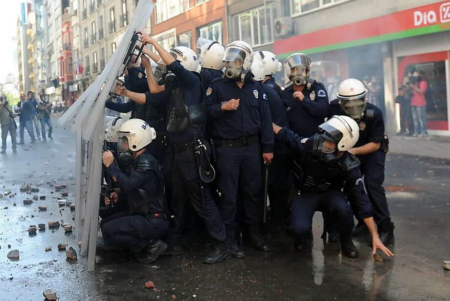 Mayday! Mayday!Surrounded police take cover behind their shields during clashes with protesters at a May Day demonstration in Istanbul.