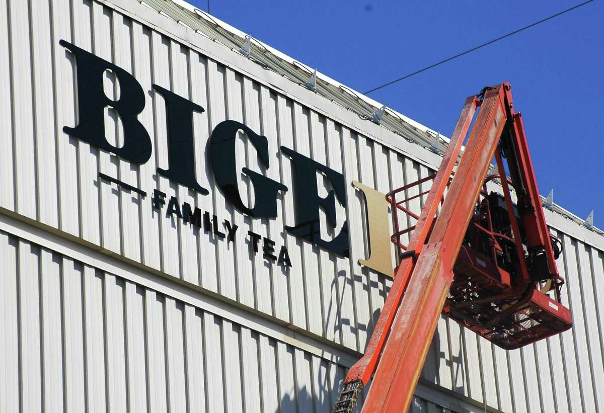Workers install new sign at Bigelow Tea headquarters with the company's redesigned logo.