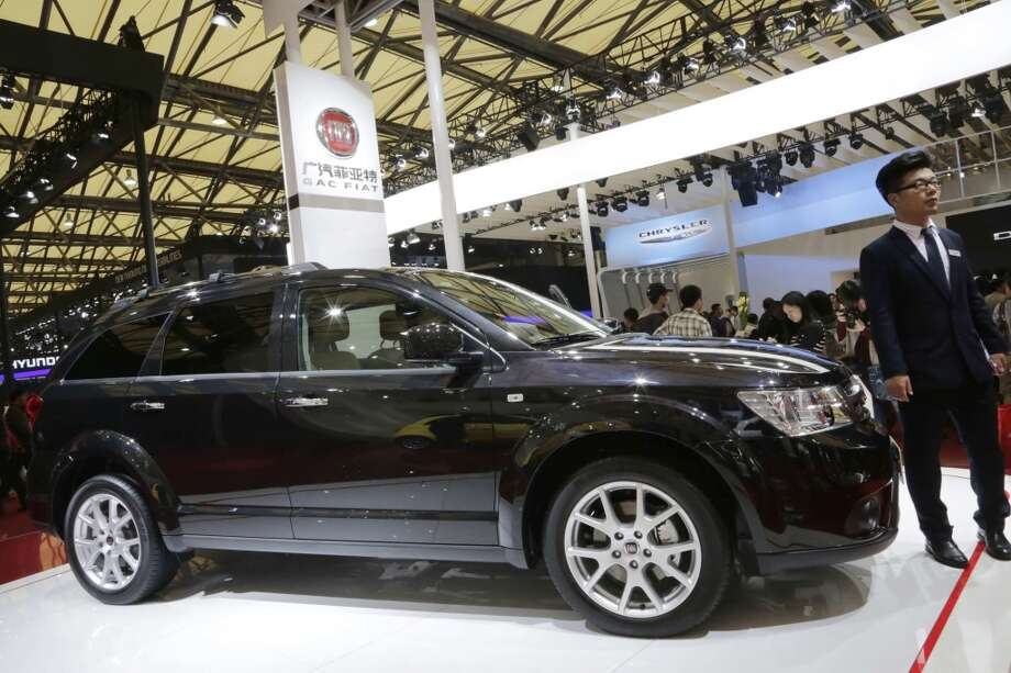 A Fiat Freemont is displayed at the automaker's booth next to Chrysler's booth at the Shanghai International Automobile Industry Exhibition (AUTO Shanghai) in Shanghai, China, Wednesday, April 24, 2013. (AP Photo/Eugene Hoshiko)
