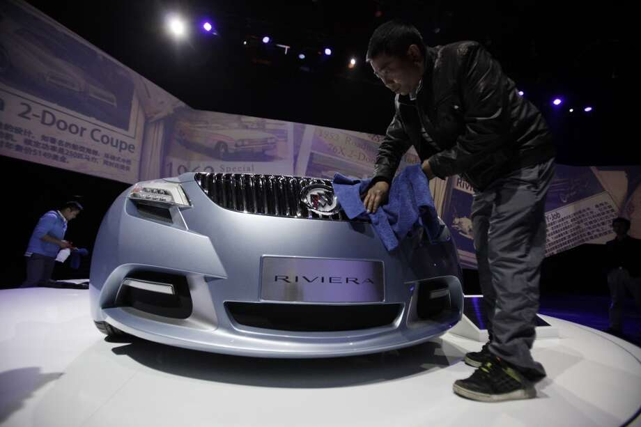 Workers clean a Buick Riviera Concept 2007 model displayed ahead of the Shanghai International Automobile Industry Exhibition (AUTO Shanghai) in Shanghai, China Friday, April 19, 2013. (AP Photo/Eugene Hoshiko)