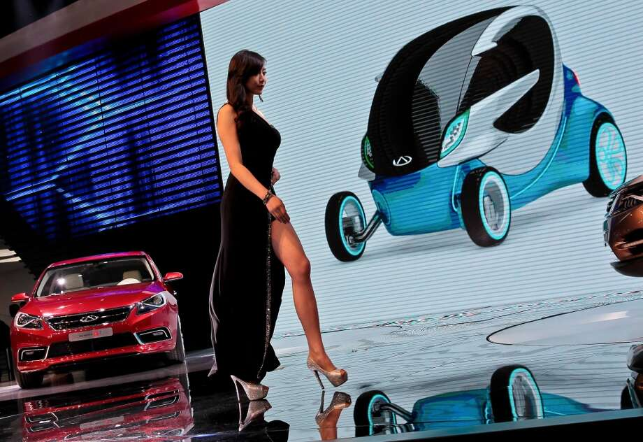 A model walks past Alpha 7 car, left, and @ANT2.0 concept car shown on the screen, made by Chinese automaker Chery on display at the Shanghai International Automobile Industry Exhibition (AUTO Shanghai) media day in Shanghai Saturday, April 20, 2013. (AP Photo) CHINA OUT