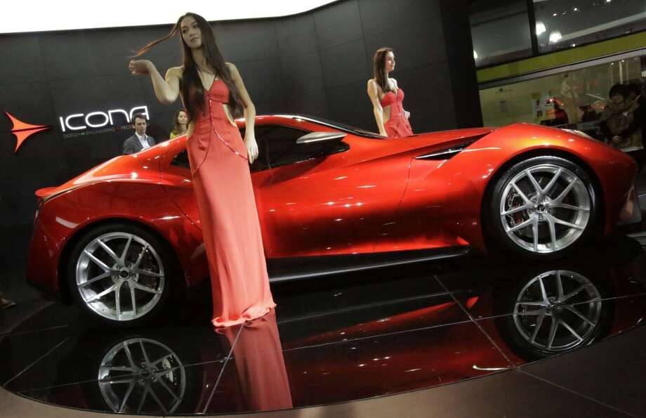 Models pose next to an Icona Vulcano at the Shanghai International Automobile Industry Exhibition (AUTO Shanghai) media day in Shanghai, China Saturday, April 20, 2013. (AP Photo/Eugene Hoshiko)