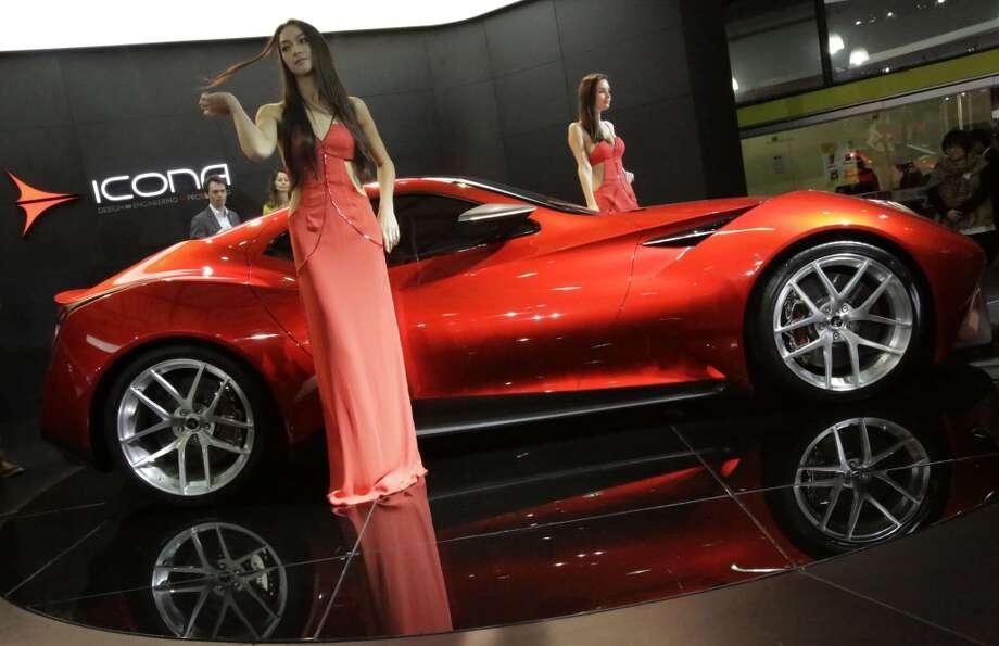 Models pose next to an Icona Vulcano at the Shanghai International Automobile Industry Exhibition (AUTO Shanghai) media day in Shanghai, China Saturday, April 20, 2013. (AP Photo/Eugene Hoshiko)
