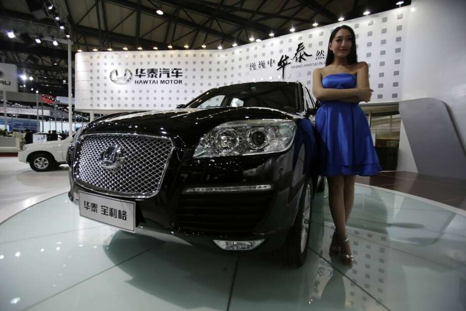 A model poses next to a Hawtai Motor Boliger SUV at the Shanghai International Automobile Industry Exhibition (AUTO Shanghai) media day in Shanghai, China Saturday, April 20, 2013. (AP Photo/Eugene Hoshiko)