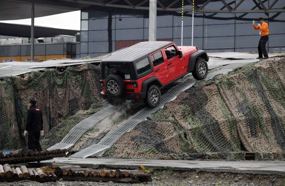 Visitor tries out the new JEEP at the Shanghai International Automobile Industry Exhibition (AUTO Shanghai) media day in Shanghai, China Saturday, April 20, 2013. (AP Photo/Eugene Hoshiko)