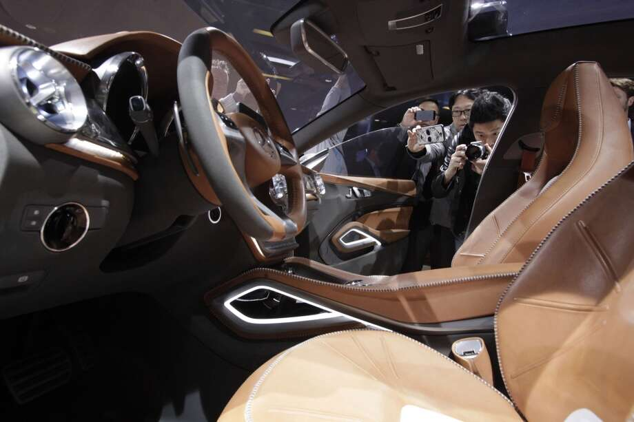 "Guests photograph the interior of Mercedes-Benz new concept car ""GLA"" during a press conference ahead of the Shanghai International Automobile Industry Exhibition (AUTO Shanghai) in Shanghai, China Friday, April 19, 2013. (AP Photo/Eugene Hoshiko)"