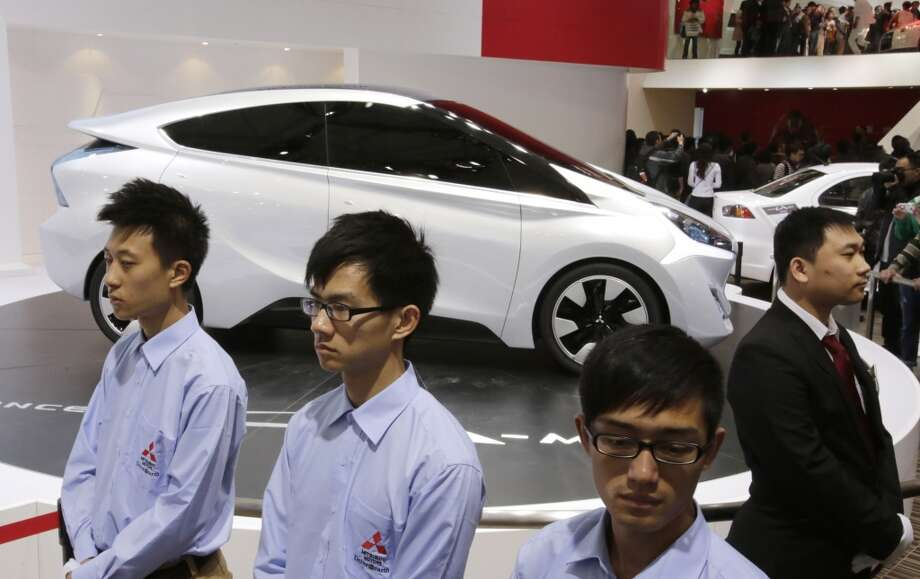 Workers stand near a Mitsubishi CA-MiEV concept car at the Shanghai International Automobile Industry Exhibition (AUTO Shanghai) in Shanghai, China Sunday, April 21, 2013. (AP Photo/Eugene Hoshiko)