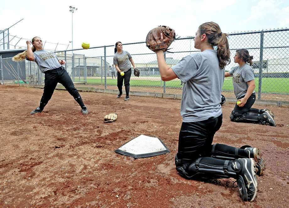 Nederland High School softball pitcher Makayla Kelly, left, warms up with Nicole Matise, right, in the bullpen during practice on Wednesday, May 1, 2013. Photo taken: Randy Edwards/The Enterprise Photo: Randy Edwards