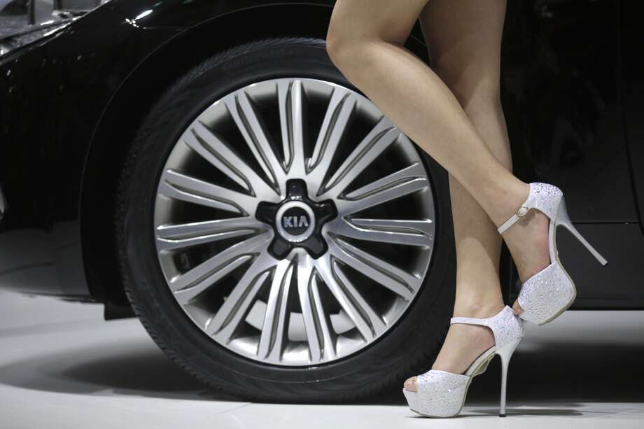 A model stands next to KIA's K9 at the Shanghai International Automobile Industry Exhibition (AUTO Shanghai) in Shanghai, China, Wednesday, April 24, 2013. (AP Photo/Eugene Hoshiko)