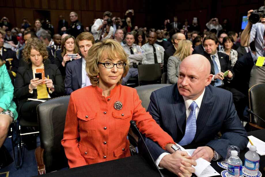 Former Arizona Rep. Gabrielle Giffords, who was seriously injured in the mass shooting that killed six people in Tucson, Ariz., two years ago, sits with her husband, Mark Kelly, a retired astronaut, prior to speaking before a Senate hearing in January on what lawmakers should do to curb gun violence. Photo: J. Scott Applewhite, STF / AP