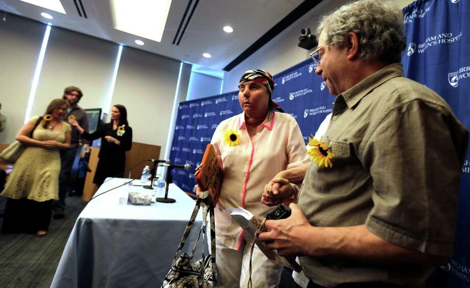 Sheldon Stein, right, holds the hand of his girlfriend Carmen Blandin Tarleton of Thetford, Vt., following a news conference at Brigham and Women's Hospital in Boston, Mass., Wednesday, May 1, 2013. The 44-year-old mother of two underwent the transplant in February after a 2007 attack in which her estranged husband doused her with industrial strength lye, burning more than 80 percent of her body. (AP Photo/Charles Krupa) Photo: Charles Krupa, STF / AP