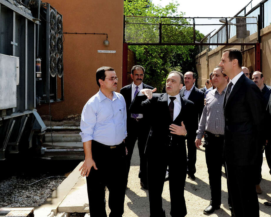 In this photo released by the Syrian official news agency SANA, President Bashar Assad, right, visits the Umayyad Electrical Station on May Day, a day after a powerful bomb hit the capital. in Damascus, Syria, Wednesday, May 1, 2013. (AP Photo/SANA) Photo: HOPD / SANA