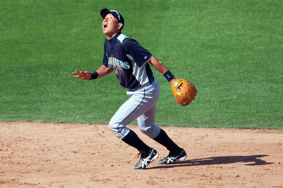 Munenori Kawasaki #61 of the Seattle Mariners attempts to catch a pop fly during the game against the Chicago Cubs at HoHoKam Stadium on March 8, 2012 in Mesa, Arizona. Photo: Rob Tringali, Getty Images / 2012 Getty Images