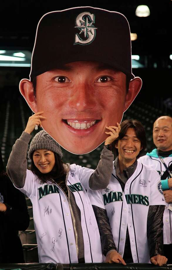 Fans hold a giant cutout of Munenori Kawasaki of the Seattle Mariners prior to the game against the Texas Rangers at Safeco Field on May 21, 2012 in Seattle, Washington. Photo: Otto Greule Jr, Getty Images / 2012 Getty Images