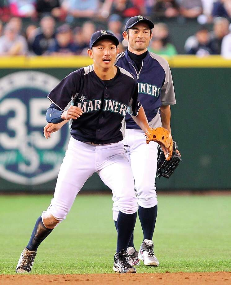 Munenori Kawasaki #61 (L) of the Seattle Mariners readies to field a ground ball at shortstop during batting practice as Ichiro Suzuki #51 looks on prior to the game against the Boston Red Sox at Safeco Field on June 30, 2012 in Seattle, Washington. Photo: Otto Greule Jr, Getty Images / 2012 Getty Images