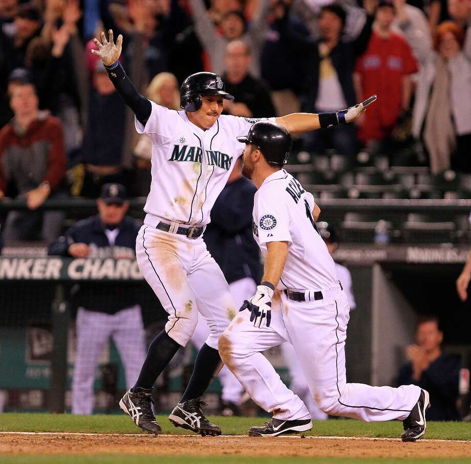 Dustin Ackley #13 of the Seattle Mariners is congratulated by Munenori Kawasaki #6 after scoring the winning run in the eleventh inning to defeat the Boston Red Sox 3-2 at Safeco Field on June 30, 2012 in Seattle, Washington. Photo: Otto Greule Jr, Getty Images / 2012 Getty Images